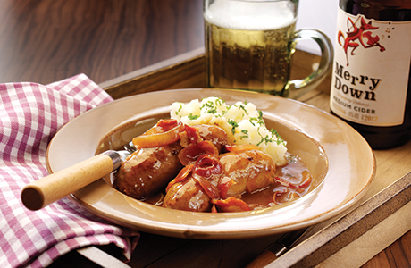 Sausages in red onion with a bottle of Merrydown cider