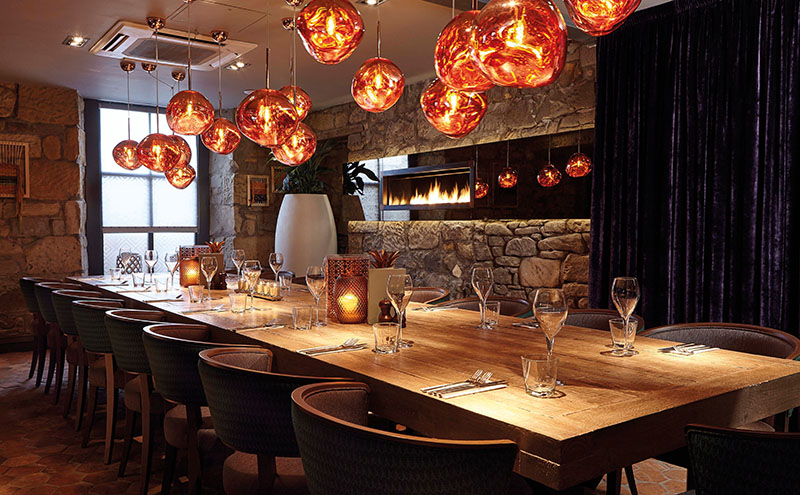 • A banqueting table, blown glass lighting and fireplace all feature in the private dining area.