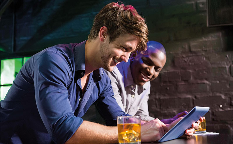 2 men with a tablet in a bar