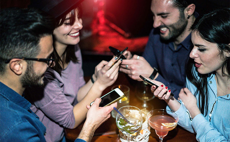 People on phones in a bar
