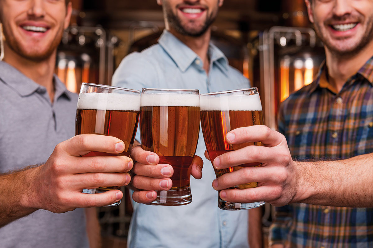 three men holding pints of lager
